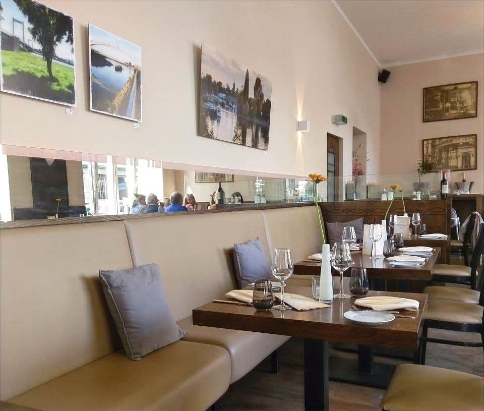 Aufnahme in den Essensbereich hinein mit brauen Sitzbänken an der Wand, eingedeckten Tischen und Fotografien an der Wand