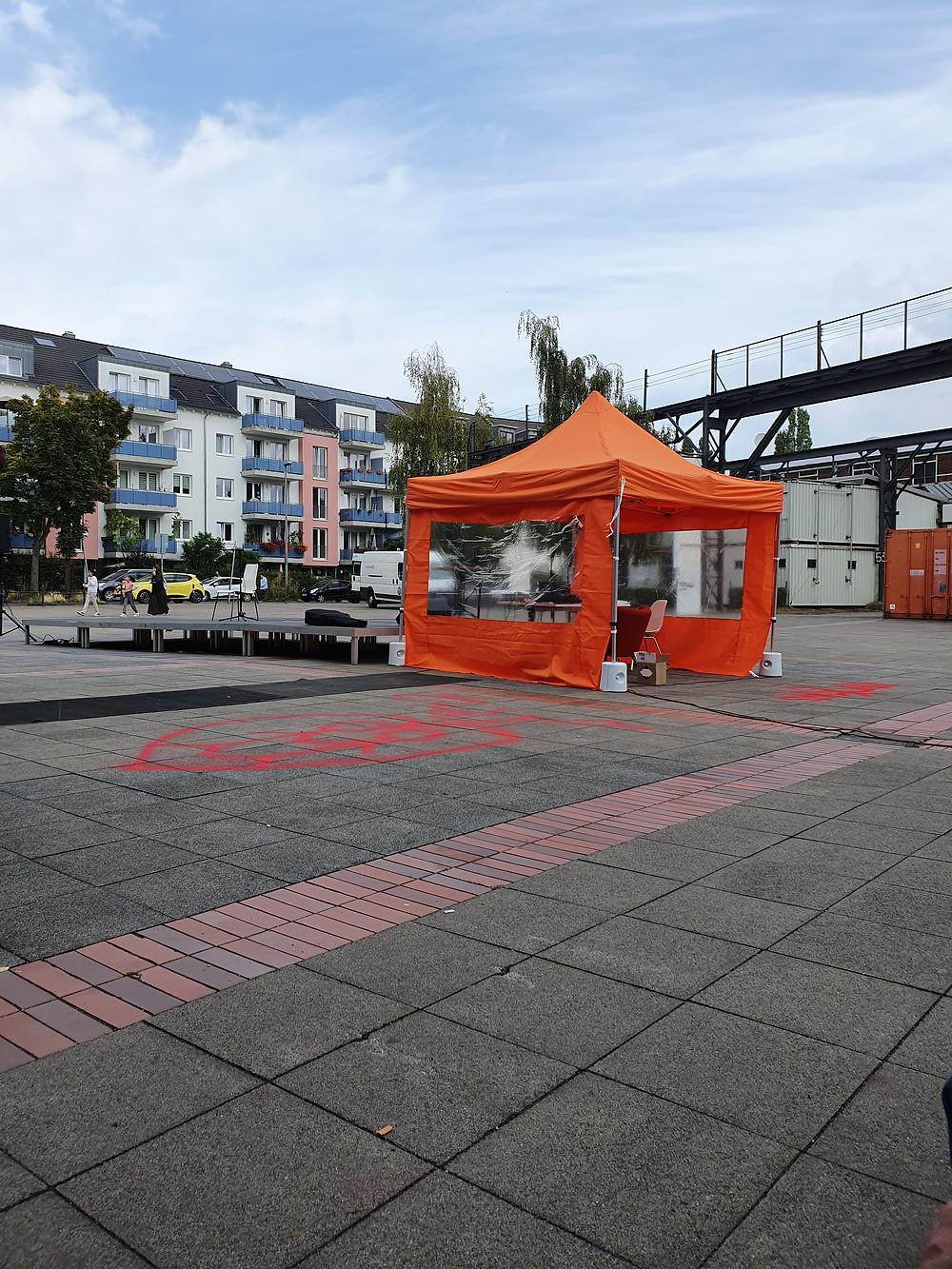 Links ist eine Bühne, rechts ein orangener Pavillon für den DJ, Häuser im Hintergrund