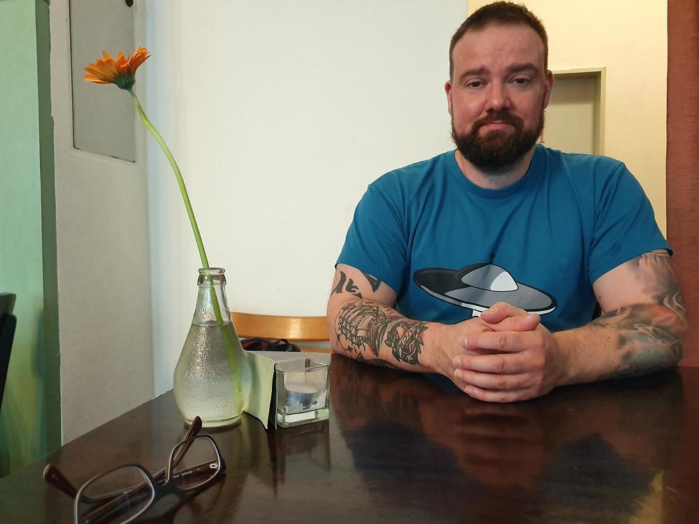 Mann mit blauem T-Shirt am braunen Tisch mit Vase und Bume links
