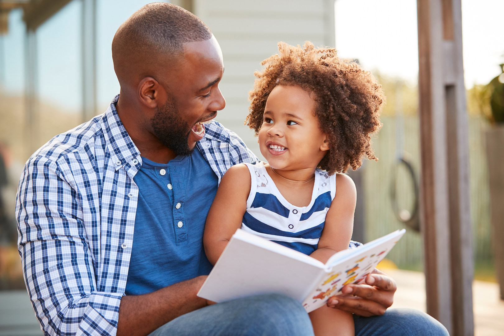 Young black father and daughter reading