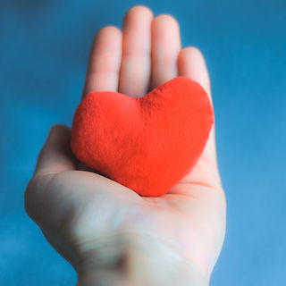 close-up-shot-of-hand-holding-soft-red-heart-on-blue-background-happy-valentine-love-care_