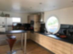La cuisine moderne, fonctionnelle, lumineuse, avec une vue sur océan via les crédences en miroir