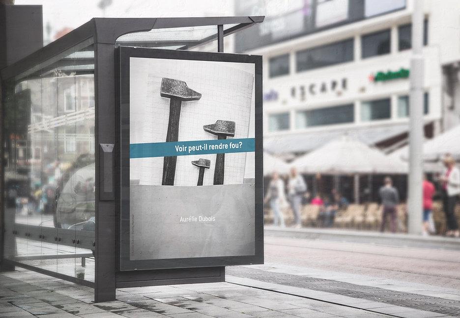 """Aurelie Dubois artiste de garde présente son affiche d'exposition sur panneau publicitaire d'arret de tramway. Logo Artiste de garde avec la mention """"Voir peut-il rendre fou?"""""""