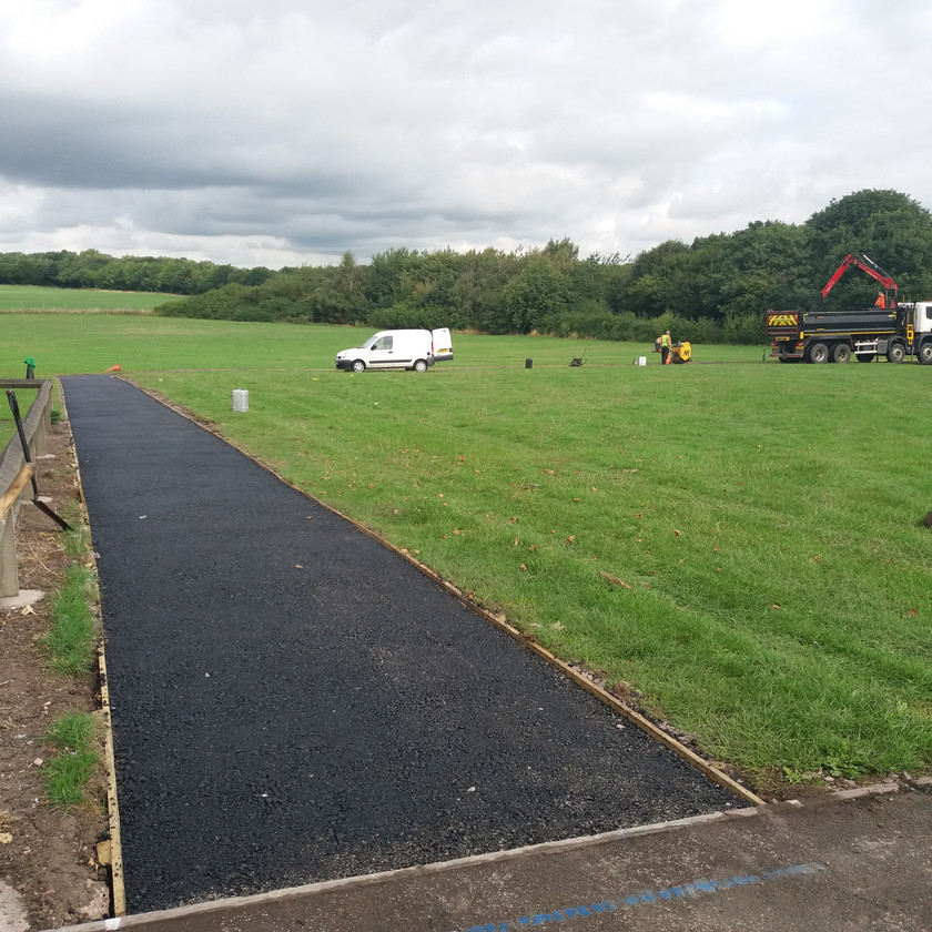 Newly paved running track by Hilton Main Construction at West Midlands school with grab wagon and crew