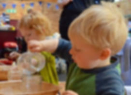child pouring activity at Glendon Farm Montessori and Forest School Nursery