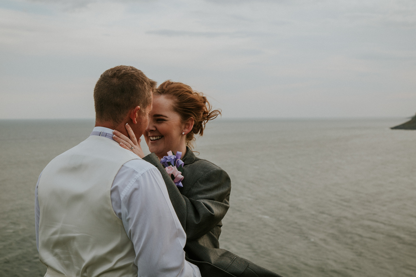 bride and groom cuddling on clifftop in langland bay