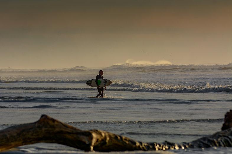 Un surfeur qui rentre dans l'eau