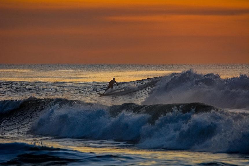 Un surfeur au couché de soleil sur la plage en Gironde