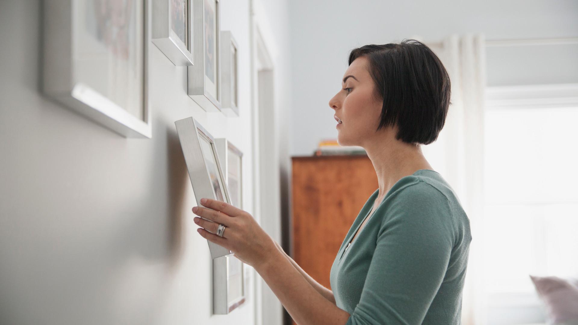 Woman Hanging Framed Photos