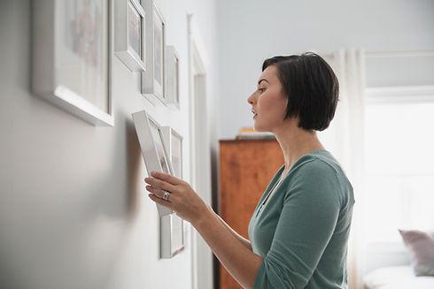 Mulher pendurado fotos emolduradas