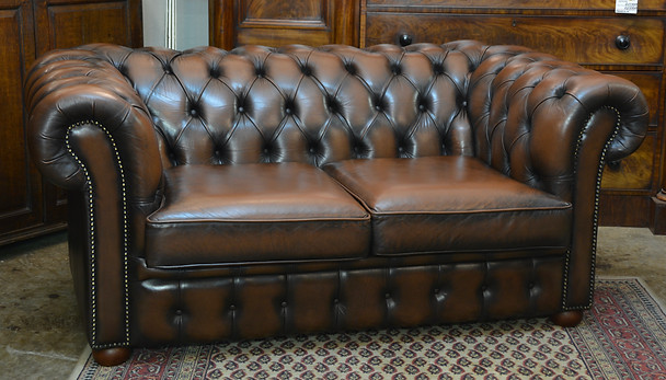 A two seater brown leather Chesterfield. R22995