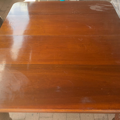 A Victorian table with heat and water damage