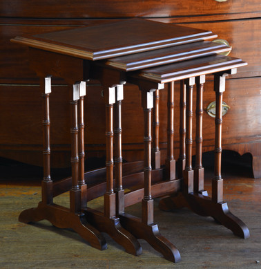A nest of three mahogany Edwardian style Tables, with tooled leather tops. R4995