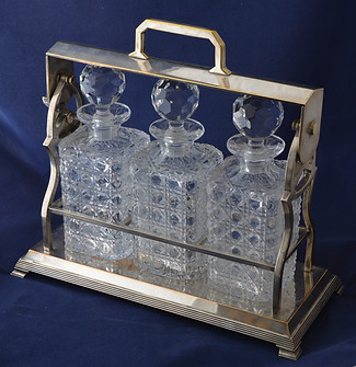 An Edwardian silver-plated Tantalus with three hobnail cut glass decanters. R6995