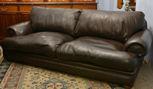A well worn leather Three Seater Sofa. R16995