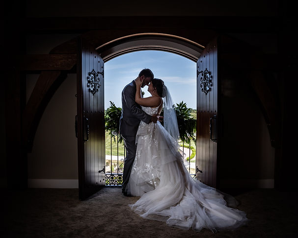 Bride and Groom gazing at one another in front of ornate wooden doors opening to balcony overlooking manicured gardens