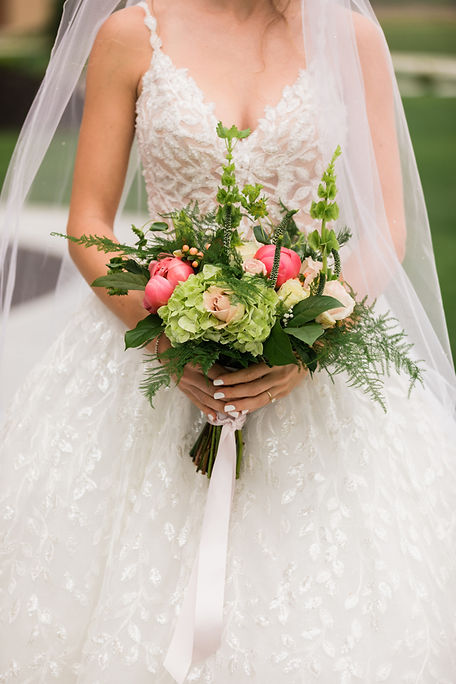 Closeup of bride's hands holding boquet with pink roses