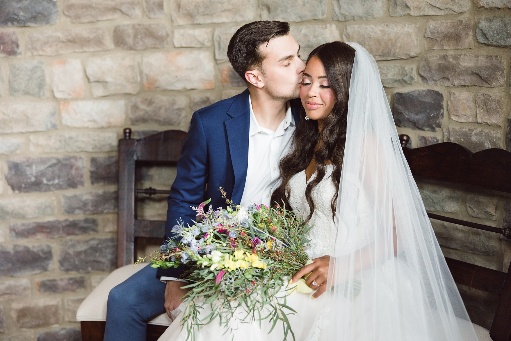 Groom kissing bride's forehead, set against The English Barn stone wall