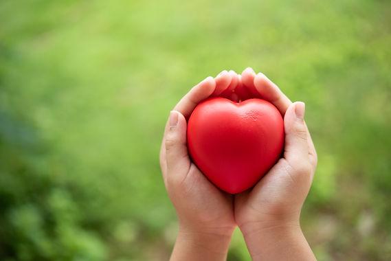 child-holding-red-rubber-heart.jpg