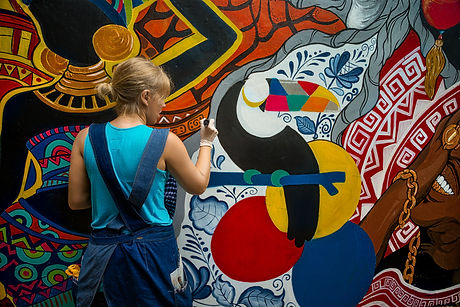 Cheerful young woman painting on the wa