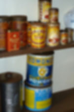 Well-worn tins of Edmonds Baking and Custard Powder stacked on a shelf.