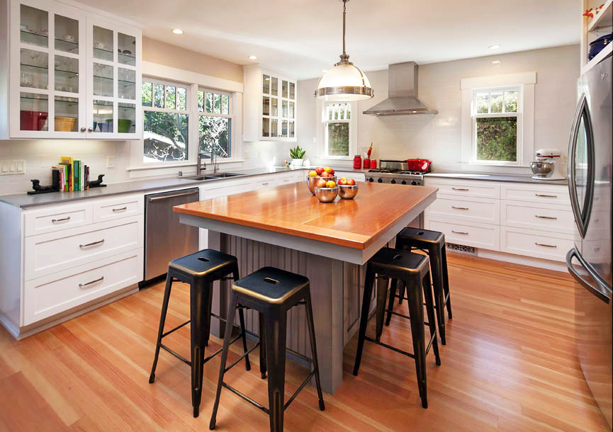 Transitional kitchen with white shaker cabinets and island with wood top. Cherry wood floors and white walls