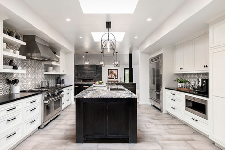 Large open kitchen with white cabinets and black painted island. Tile floors, skylights and coffee bar station
