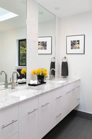 Modern white floating bathroom vanity with geometric wall tile