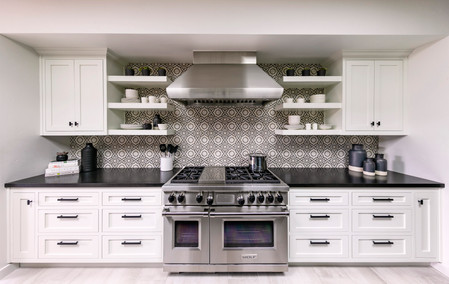 Kitchen range wall with white Shaker cabinets, open shelving, large stainless steel Wolf range, and patterned tile backsplash design