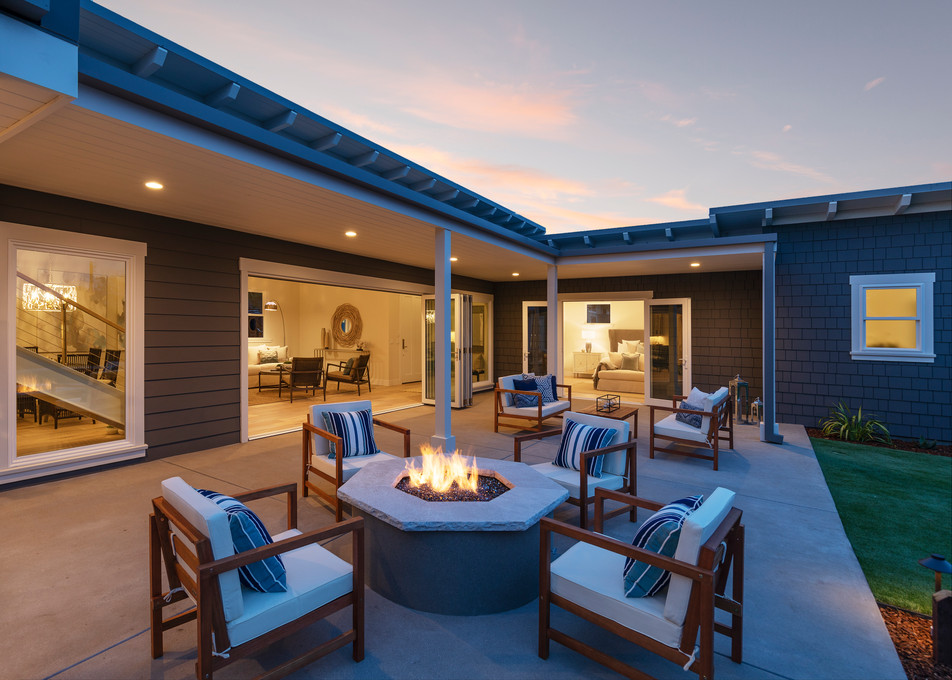 Outdoor modern firepit seating area with open doors from house for indoor/outdoor living