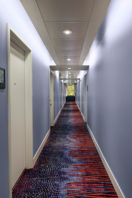 Hotel hallway with bright, colorful carpet