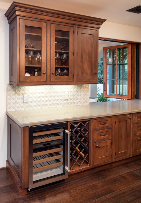 Custom stained wood cabinetry with wine refridgerator, wine storage, kitchen bi-fold pass through window, white tiled backsplash