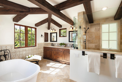 Spanish Mediterranean master bathroom interior design in Santa Barbara. Wood beams, hand painted wall tile wainscotting, limestone shower and floors, soaking tug