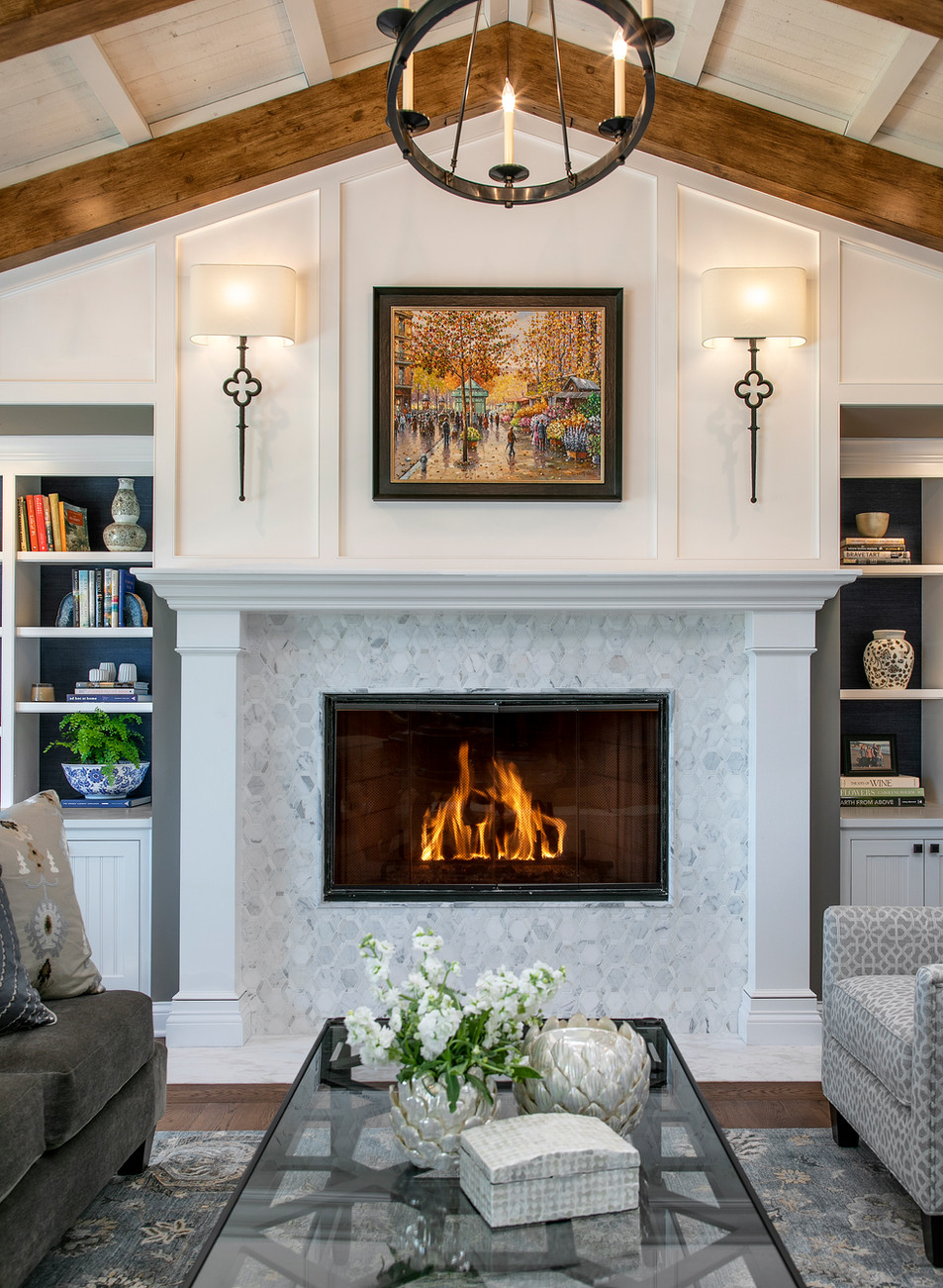 Wine Country Living fireplace with white painted mantle and wood paneling, marble tile surround and built in bookcases. Vaulted ceiling with beams.