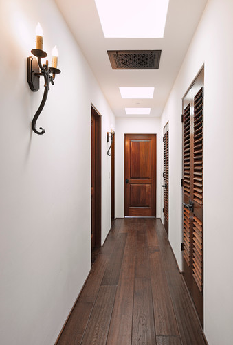 Spanish Mediterranean Elegance hallway with wood floors, iron sconces, decorative return air vent, skylights and louvered doors