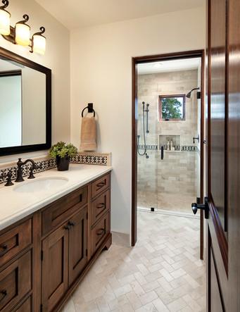 Spanish Mediterranean Elegance bathroom with custom dark wood vanity, limestone floors, iron and bronze fixtures