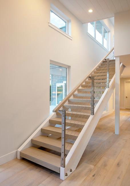 Modern white steel staircase with wood treads. Light oak wood floor.