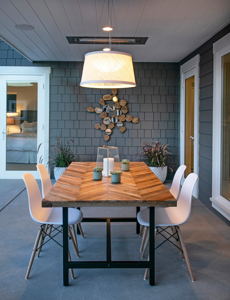 Modern outdoor dining area with grey shingled wall, pendent light and chevron top wood table