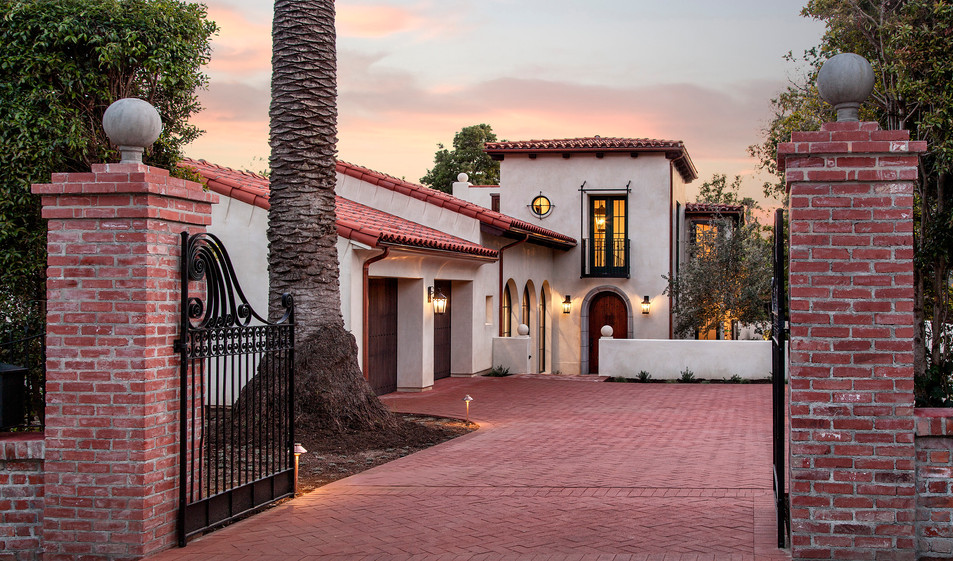 Santa Barbara Mediterranean exteropr with brick driveway and pilliars, custom iron gate, arched doors and windows