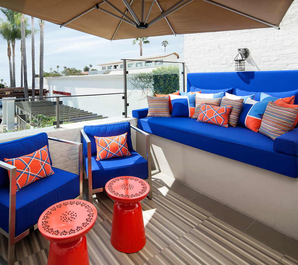 Outdoor patio furniture with custom pillows, blue and orange design palette