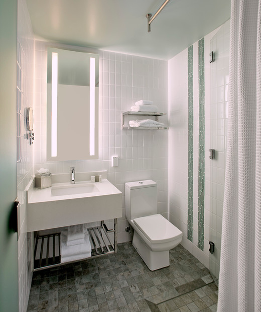 Hotel bathroom with white tile and floating vanity