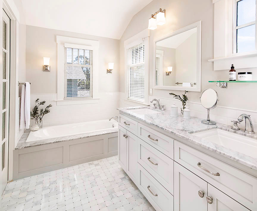 Classic bathroom with white shaker vaity, built in tub with wood panling, light gray walls and marble floor tile