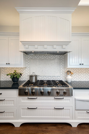 Wine Country Living transitional cooking range with decorative marble backsplash tile, white painted cabinets and wood hood