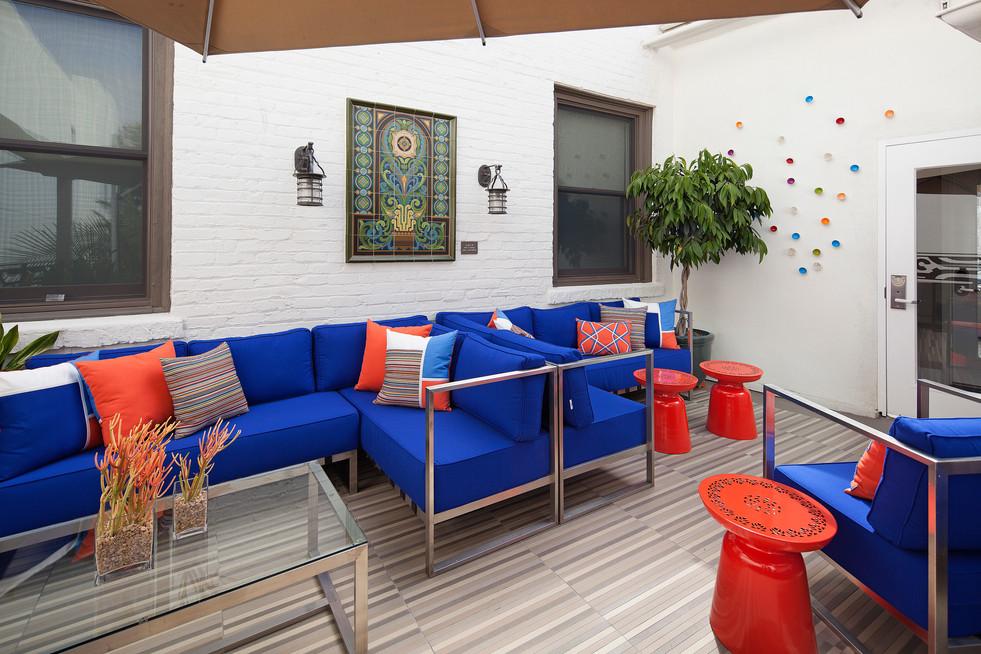 Bright interior design in Santa Barbara of hotel patio with blue furniture cushions and orange accents