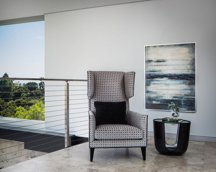 Modern Oasis modern wingback chair in grey velvet, with side table and oversized artwork on mezzanine