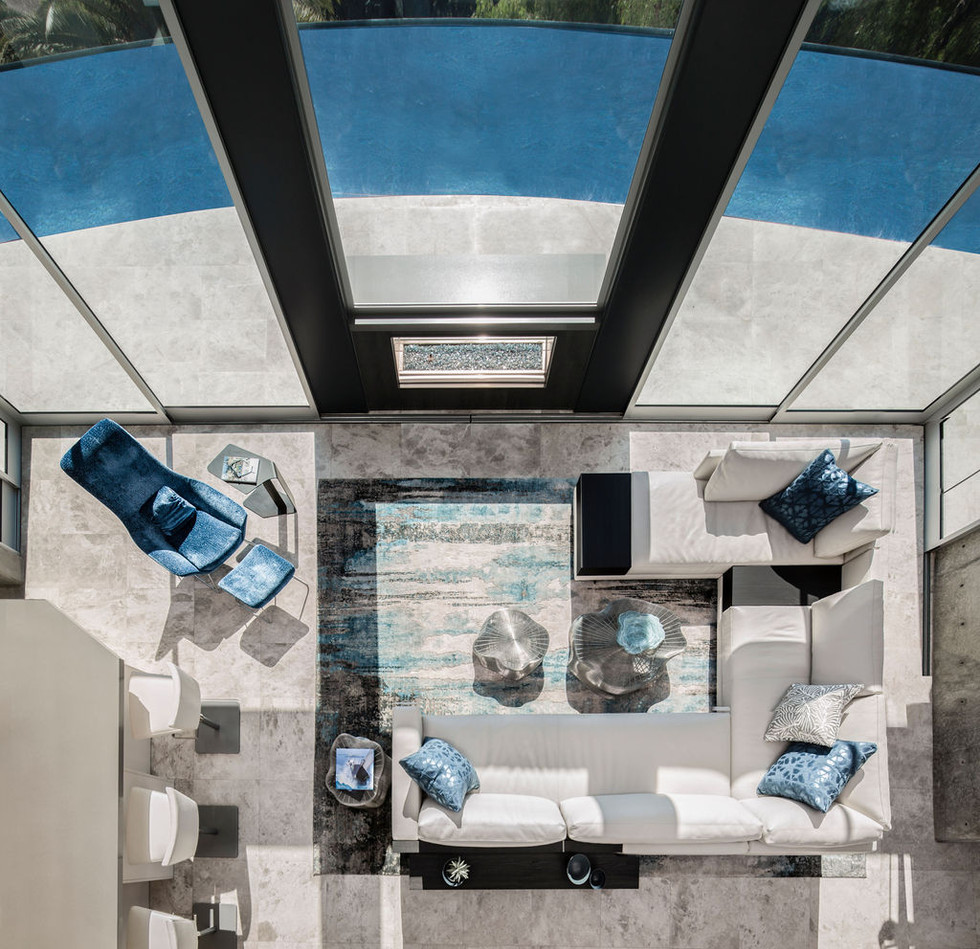 Modern Oasis modern living room interior design in Santa Barbara with double height glass walls, curved infinity pool, poliform sectional in white leather, blue accents