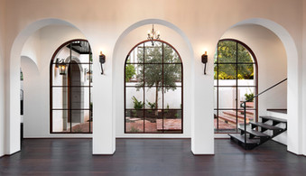 Spanish Mediterranean Elegance arched hallway and windows with white walls, iron lighting and dark wood floors