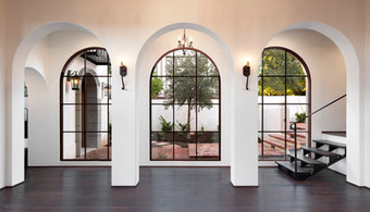 Spanish Mediterranean Elegance arched hallway and windows with white walls, iron lighting and dark wood floors