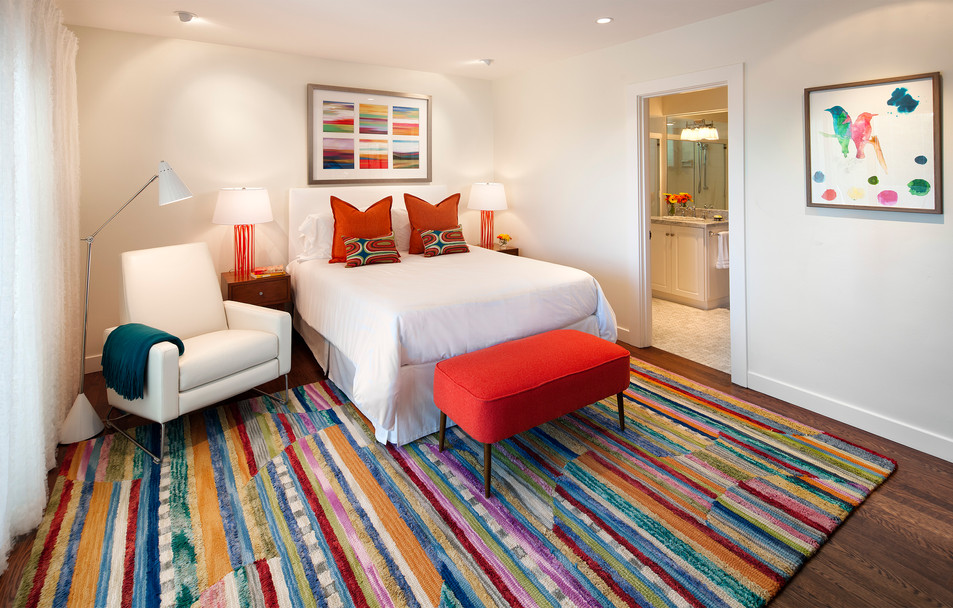 Colorful Modernbedroom with white walls and colorful rug, orange bench and bright pillows