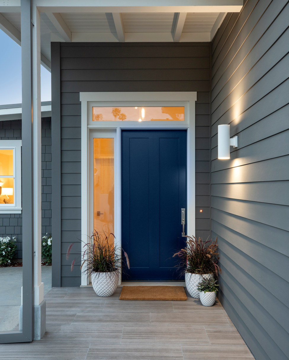 Grey house with dark blue front door, side lite and white trim.